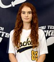 female with long red hair wearing a softball jersey