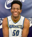 Young man smiling wearing a basketball uniform