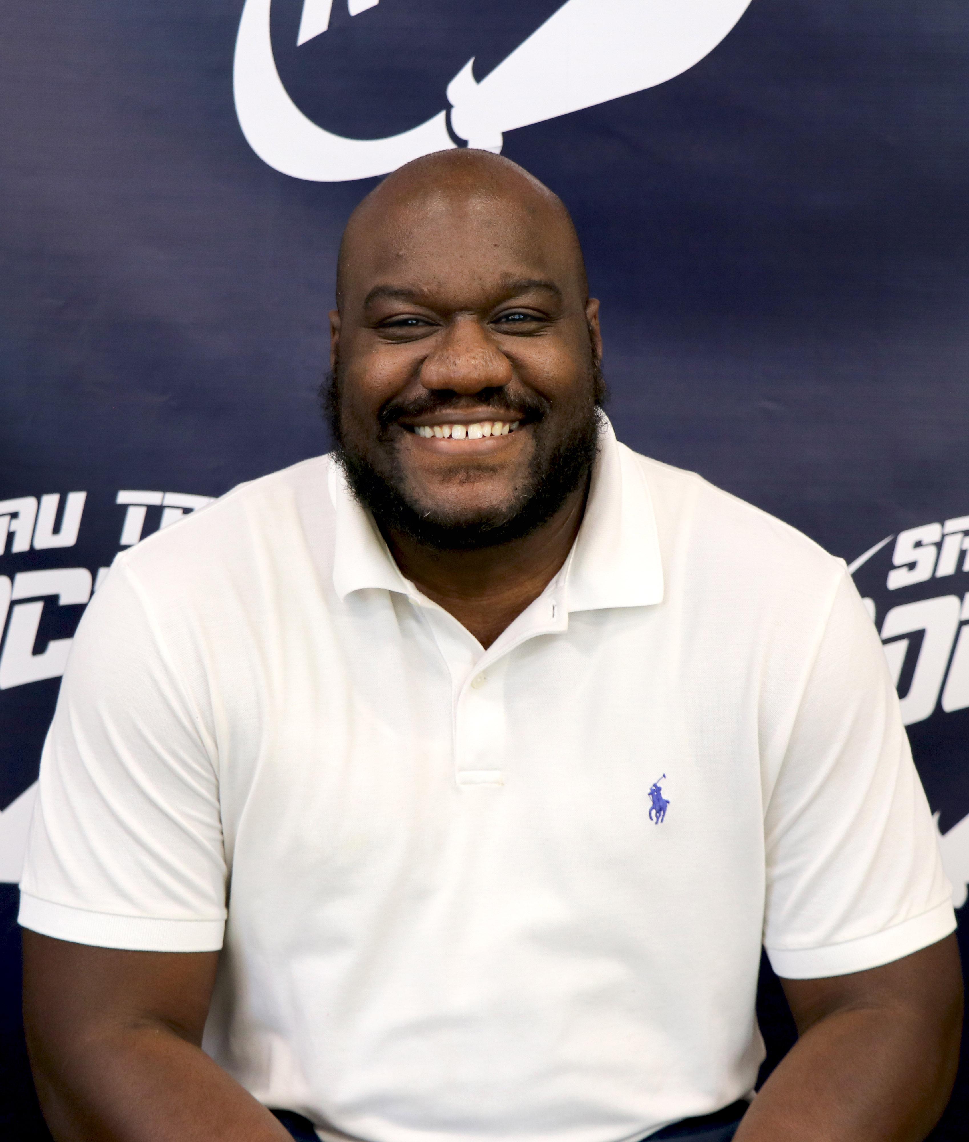 smiling man in white polo